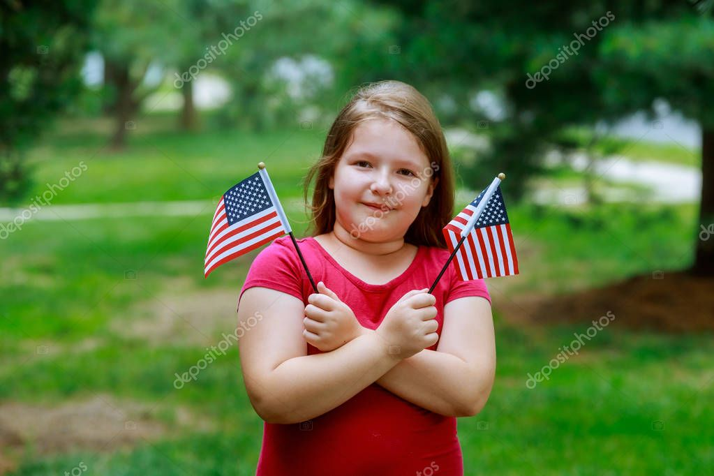 Laughing little girl with long curly blond hair holding american flag and waving it, outdoor portrait on sunny day in Independence Day and Flag Day