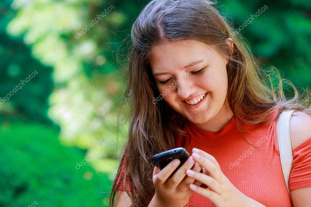 Smiling young good teen girl reading messages in social networks on a cell phone