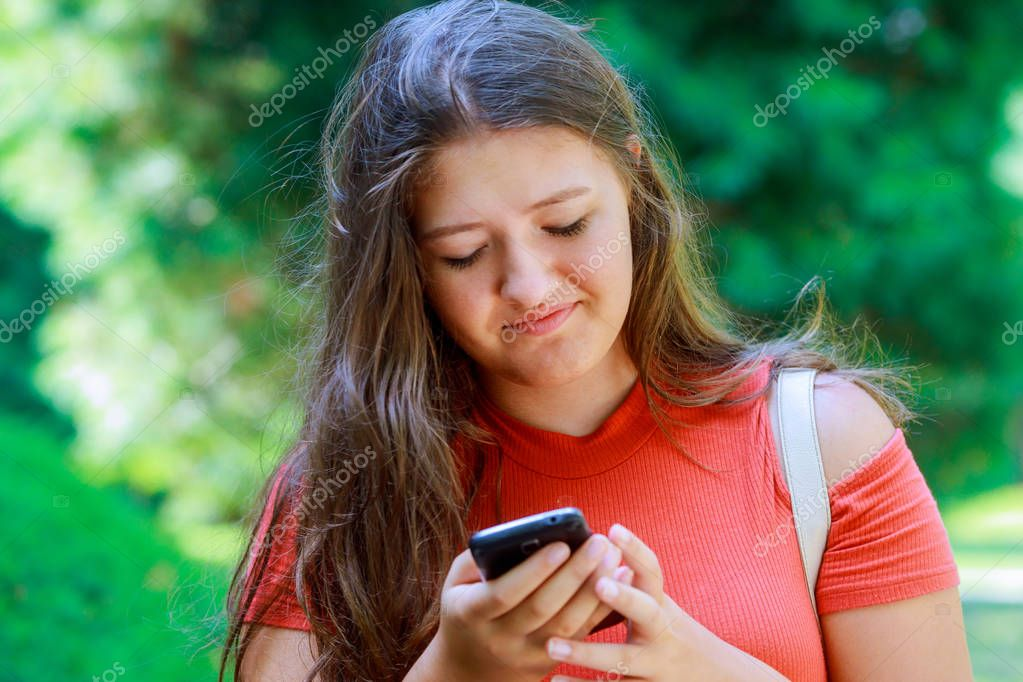 Portrait of a beautiful teen girl typing messages on the smart phone in a park with green unfocused background