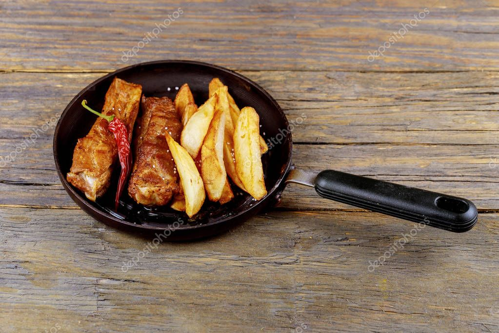 Fried ribs with potatoes in a frying pan on a wooden rustic table. Close up and selective focus. on a plate on a low fat healthy eating concept.