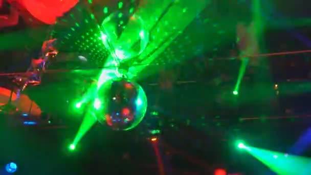 Raggi laser multi-colored e nebbia in scuro procedere da un punto.