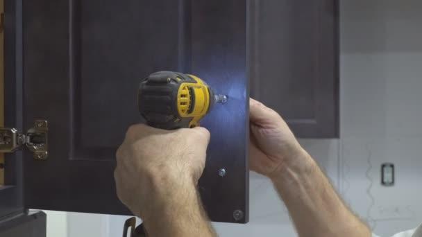 Montage der Türgriffe auf Küchenschränke mit einem Schraubendreher
