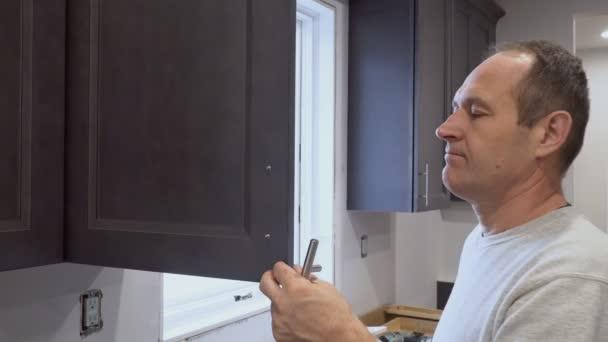 Hand auf den Griff Montagetür im Küchenschrank mit einem Schraubendreher