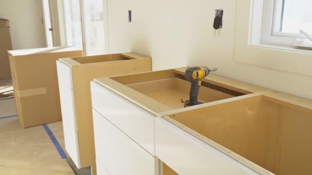 Reparatur-Mann im Overall Reparatur Kabinett Scharnier In Küche
