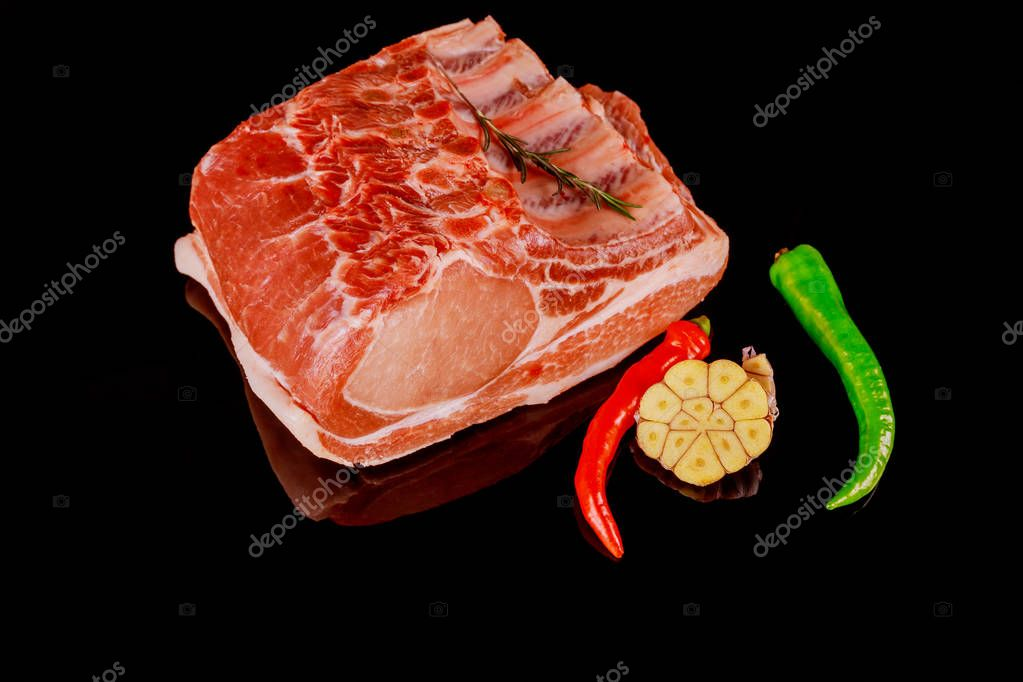 Raw pork ribs with ingredients on dark black background. Ready for cooking.