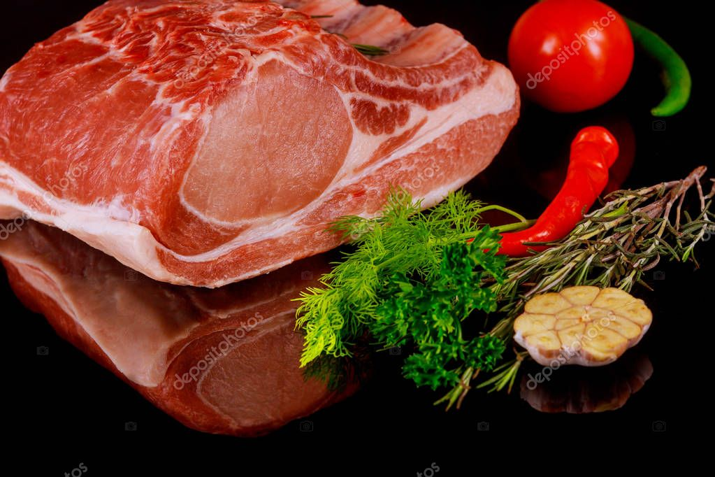 Raw juicy steaks on a black board background. Rib eye steak on the fillet with cherry tomatoes, hot pepper and herbs.
