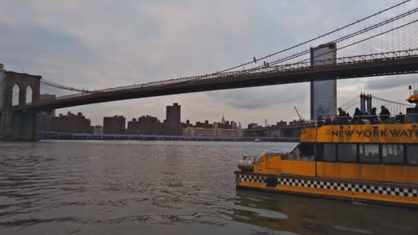 NEW YORK, NEW YORK, USA - december 30, 2018: Manhattan skyscrapers and Brooklyn Bridge NYC yellow water taxi