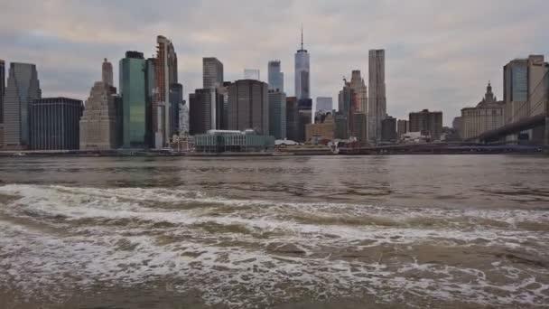 New York, New York, Usa - 30. prosince 2018: Outdooors pohled na Nyc New Yorku Brooklyn Bridge Park east River, Panorama Panorama při západu slunce, mrakodrapy, budov, vlny, žluté výletní loď, taxi
