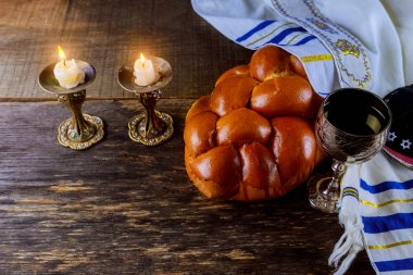 Shabbat eve table candles and cup of wine with covered challah bread,