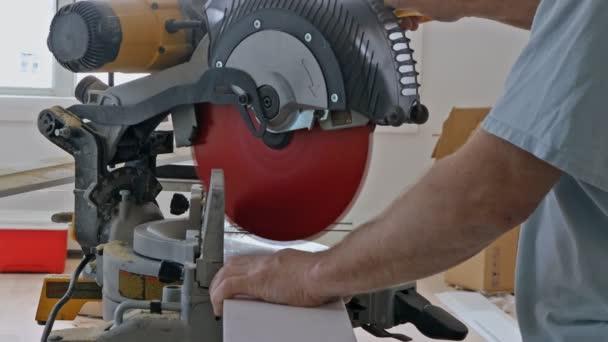 Pracovník řeže dřevěnou podložku na motorové pilce