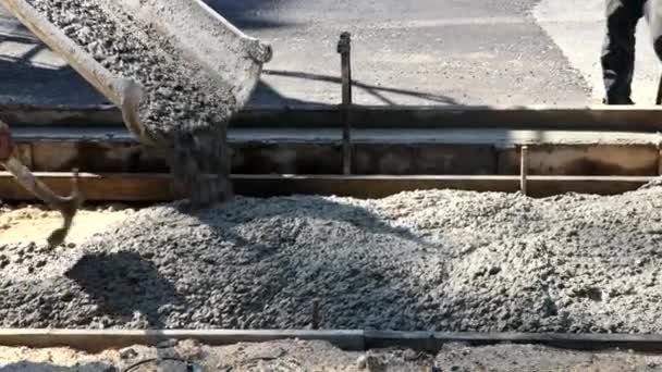 Stavební dělník nalévá cement na chodník v betonárnách