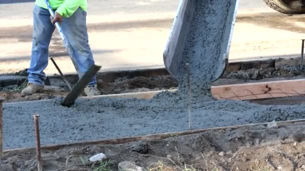 Stavbaři na staveništi plní bednění cementárnami v procesu vytváření nového chodníku betonu
