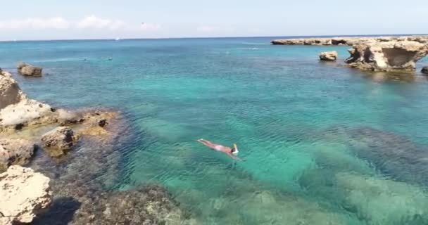 Summer image of beautiful girl swimming and lying on the back in the turquese sea water. Slim tanned body. Amazing sea landscape. Happy vacation and relaxing. Cyprus Green bay.