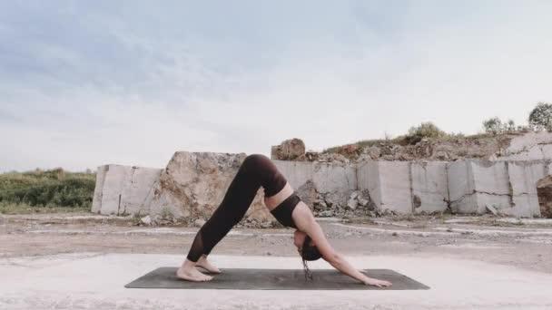 Yoga-Mädchen macht Übungen auf einem Marmorbruch bei Sonnenaufgang in Sibirien