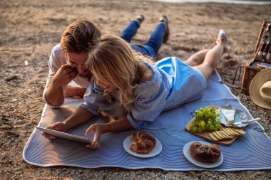 Couple in love on a picnic date using tablet.