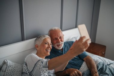 Senior couple making a selfie in bed.