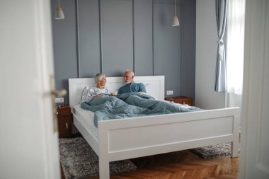 Senior couple enjoying time together in bed.