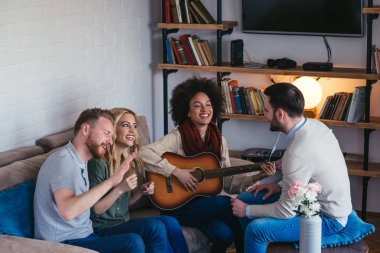 Friends making a party with a guitar and good mood.