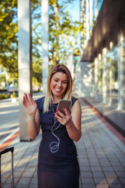 A beautiful young professionally dressed woman happily browsing her phone.