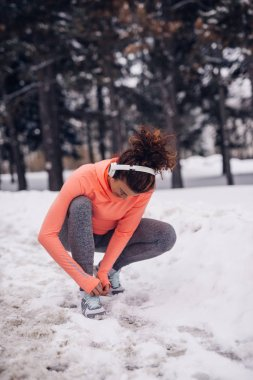 Athlete woman preparing for a run while listening to the music outdoors in the winter.