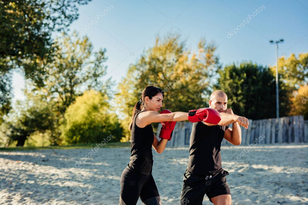 A young beautiful fit woman is training with her personal trainer.