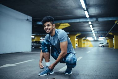 Photo of a smiling african american athlete man getting ready for a run.