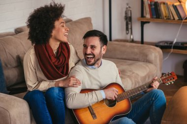 Portrait of a young lovely couple enjoying singing and playing guitar together.