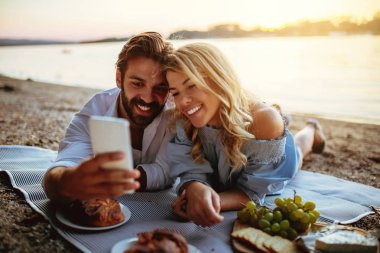 Young couple taking a photo with mobile phone on a picnic date.