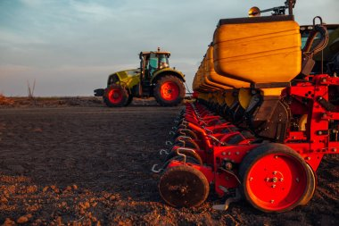 Shot at sunset of a tractor plowing the field.