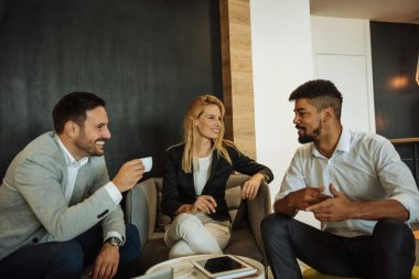 Group of young business people talking over coffee