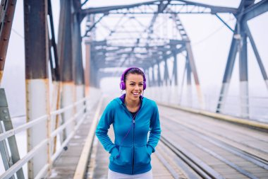 Shot of a young athlete standing on a bridge on a winter day