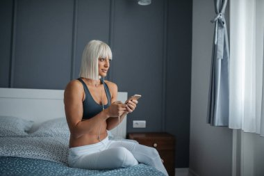 Young woman sitting on the bed , holding her mobile phone