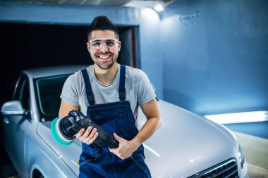 Portrait of young man holding a car polish machine in a workshop.