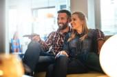 Fényképek Fénykép egy boldog fiatal pár otthon tévénézés