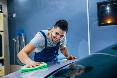 Man washing his car in a workshop.