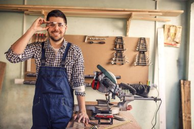 Portrait of smiling young handsome carpenter leaned on the table in workshop.