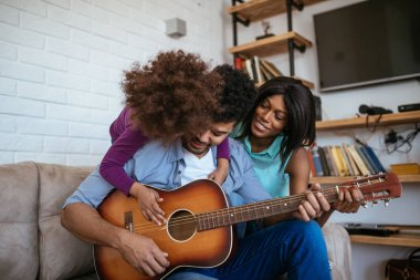 Shot of happy african american family playing guitar and singing together.