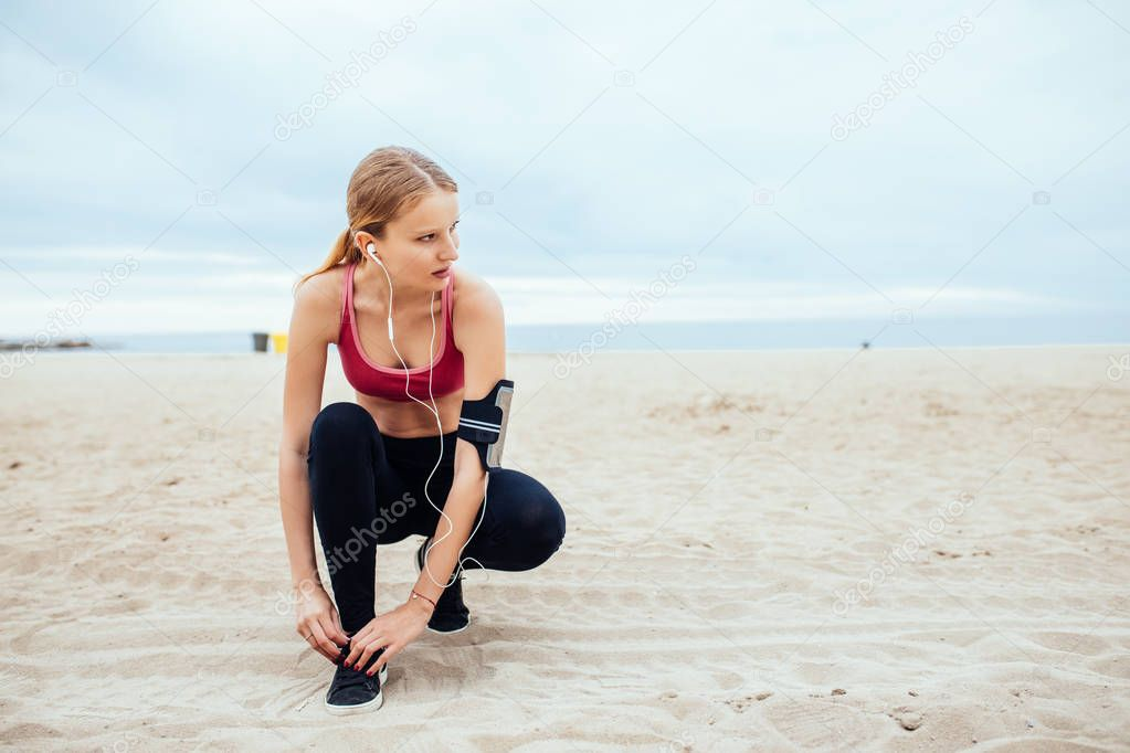 Handsome woman tying a shoe lace while running on the beach.