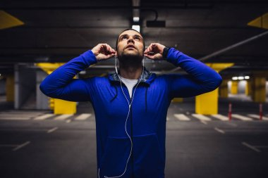 Handsome male athlete putting the earphones on.
