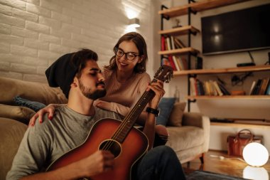 Beautiful couple playing some music on the guitar.