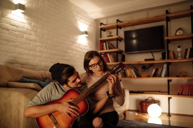 Shot of a young male teaching his girlfriend playing guitar.
