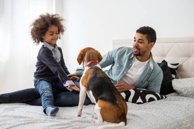 African american family spending time together with a dog in the bedroom.