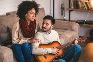 Young couple singing and playing guitar at home.