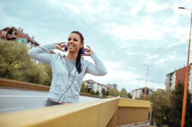 Portrait of smiling athlete woman listening to the music.