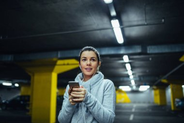 Portrait of young athlete woman using mobile during workout.