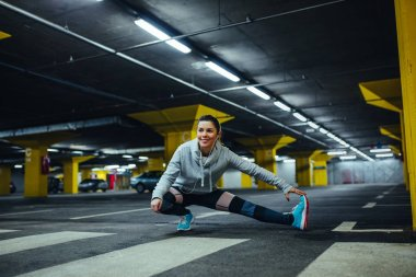 Portrait of a confident smiling athlete woman doing some stretching exercises and listening to music.