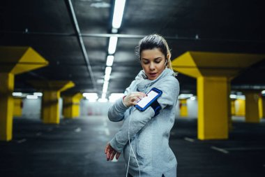 Portrait of a lovely young athlete woman using mobile phone.