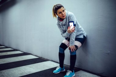 Portrait of an athlete young woman using mobile phone and listening to the music while resting.