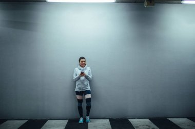 Full length portrait of an athlete woman using mobile phone and listening to the music.