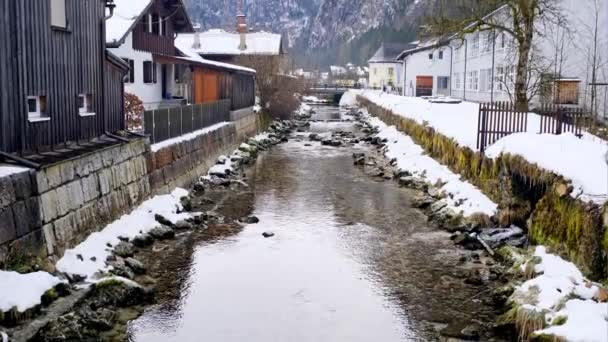 Beautiful narrow unfrozen water channel flowing between old elegant houses with mountains on background on winter day in Hallstatt, Austria